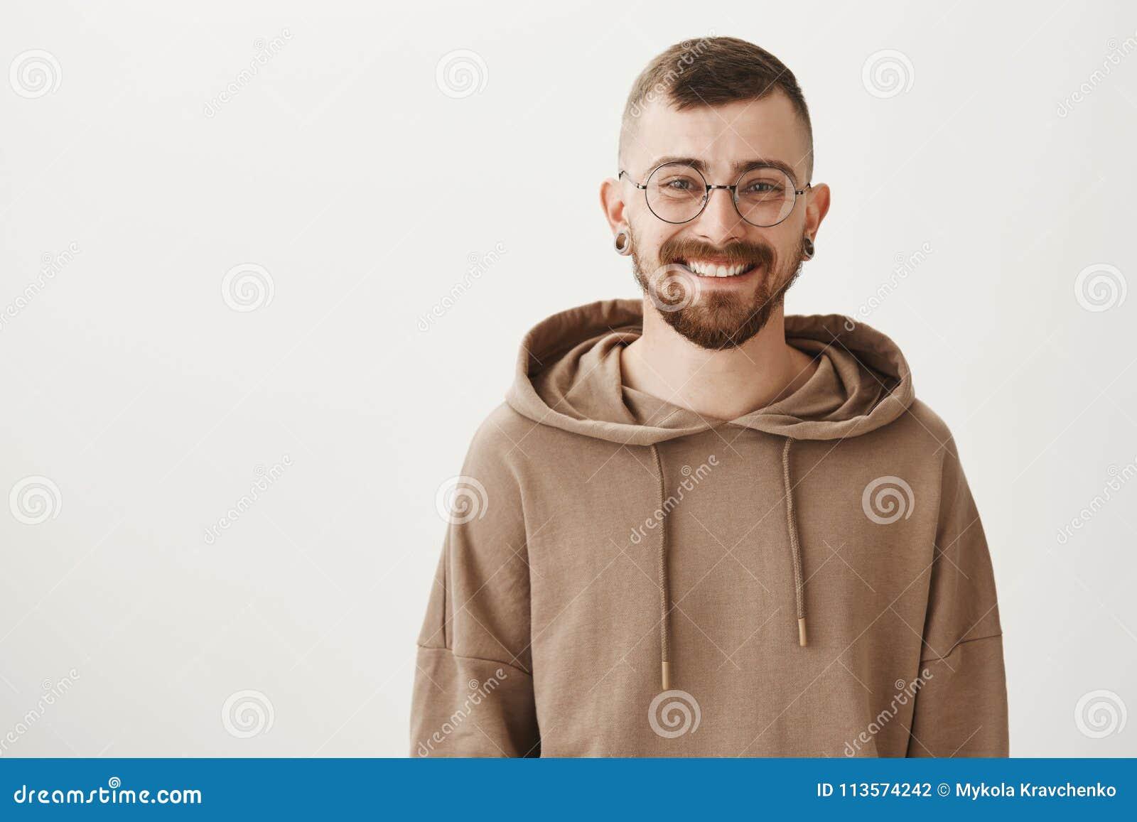 Taille-op binnenschot van vriendschappelijke knappe hipsterkerel met in kapsel en glazen die cheerfully terwijl status glimlachen