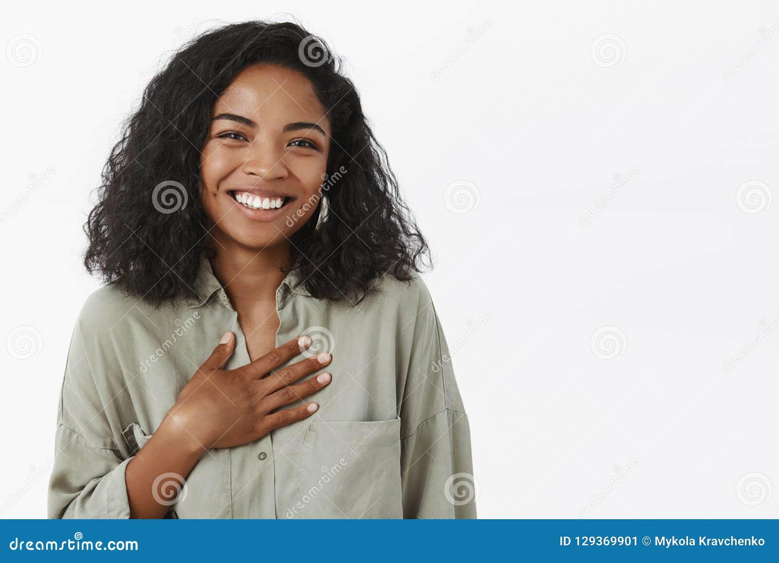 Taille-op schot van geamuseerd aantrekkelijk en modieus jong Afrikaans Amerikaans wijfje met krullend kapsel die het tevreden ont