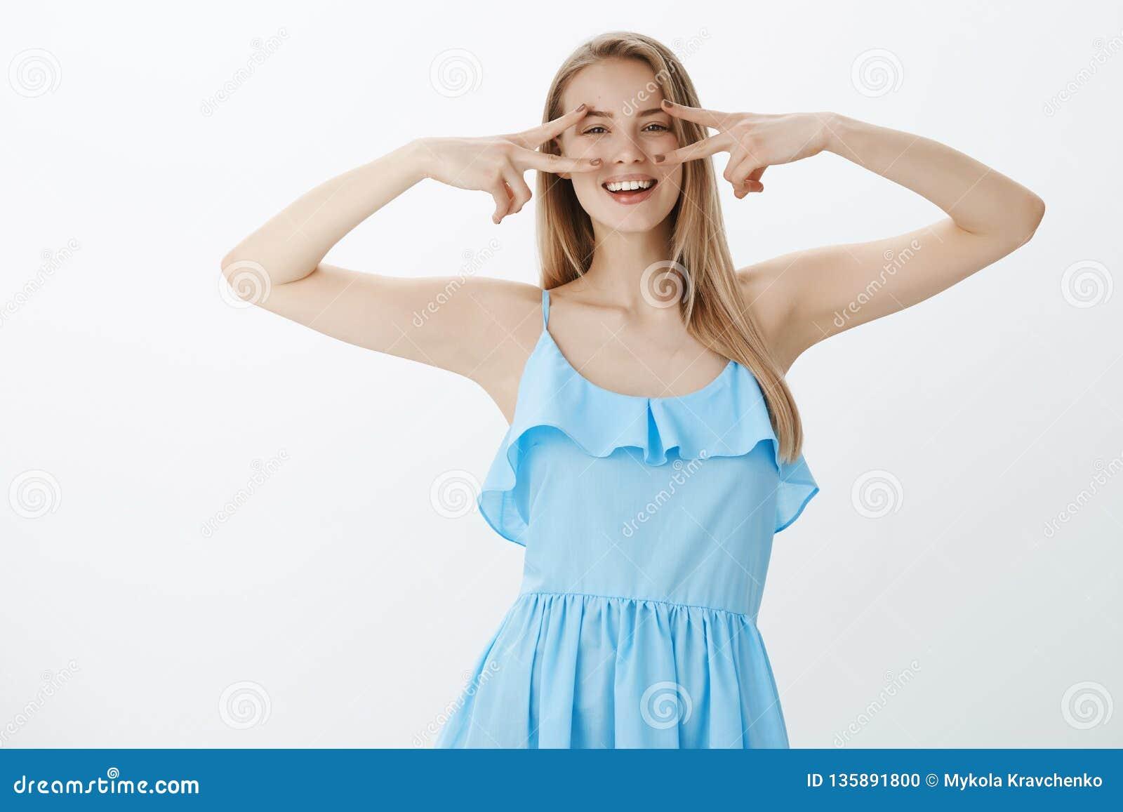 Taille-op schot van positieve, gelukkige en optimistische jonge charismatische vrouw in blauwe kleding met eerlijk haar en mollen