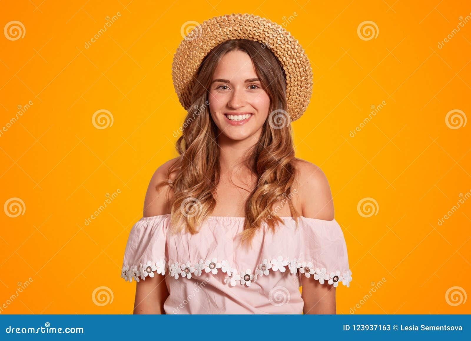 Taille vers le haut de portrait de beau jeune voyageur féminin avec plaisir avec le large sourire, peau pure saine, habillée dans