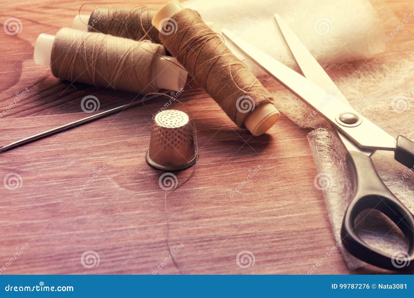 Tailor& x27; s bureau Oude naaiende houten trommels of strengen op oude houten worktable met schaar Het stemmen voor antiquiteit