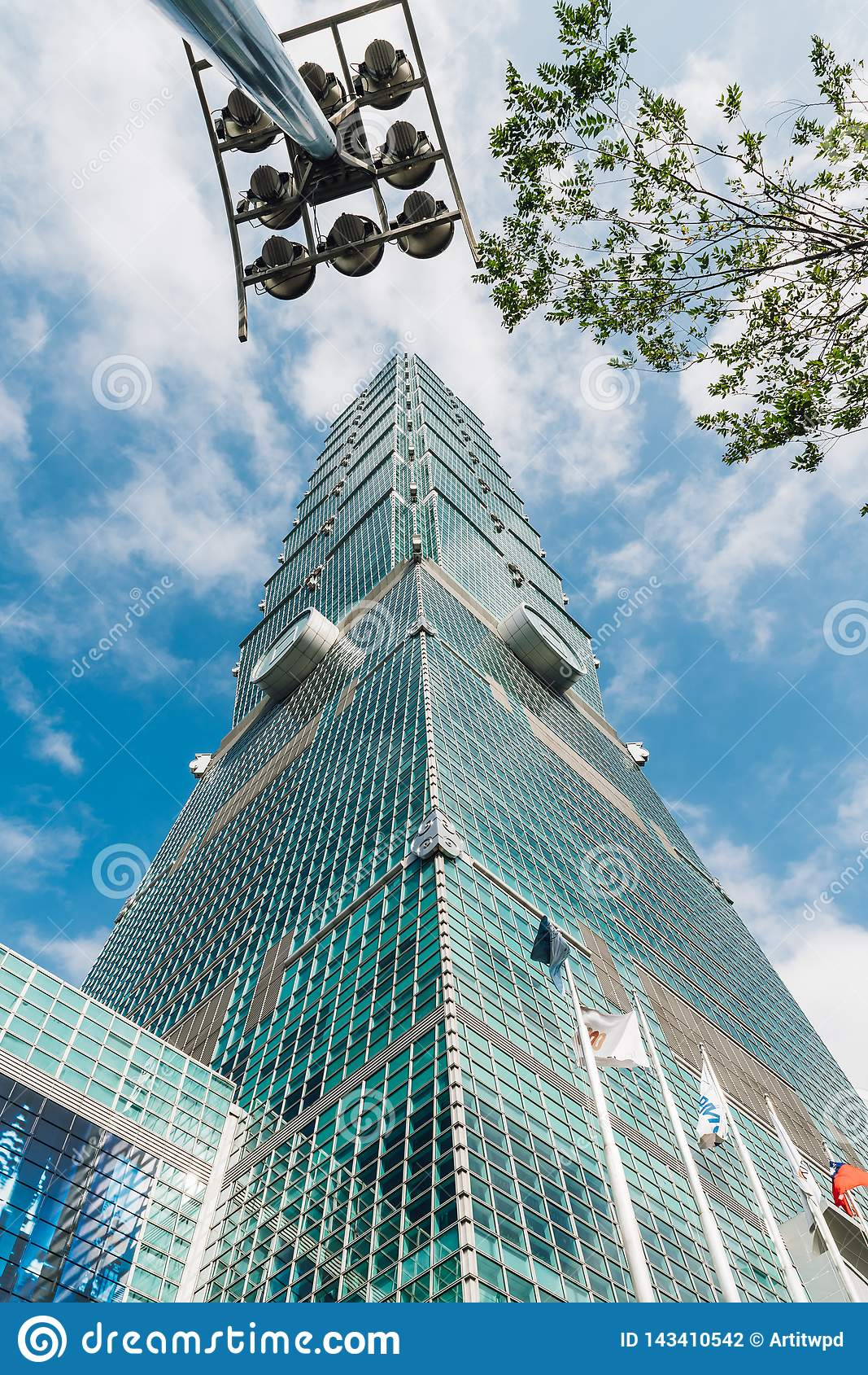 Taipei 101 byggnader med trädfilialer och byggnadsljusstolpe underifrån med det ljusa blå himmel och molnet i Taipei, Taiwan