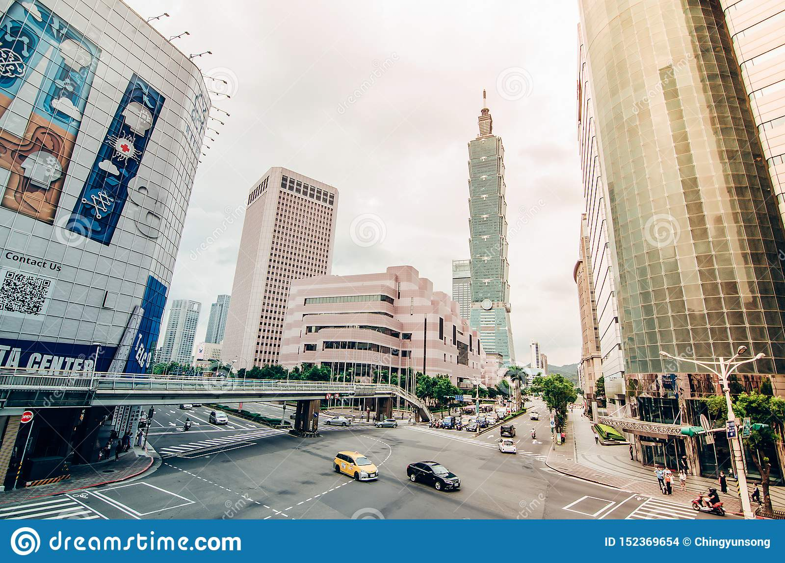 View of a busy street corner in Downtown Taipei City at rush hour with cars & buses dashing by,
