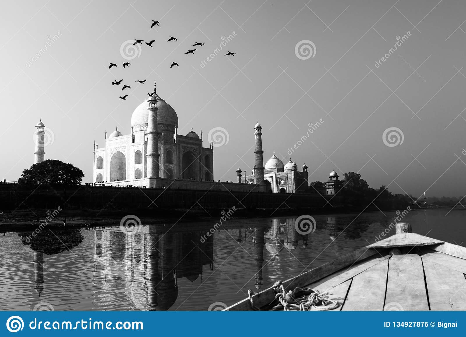 Taj Mahal reflected in Yamuna River view from wooden boat in black and white.
