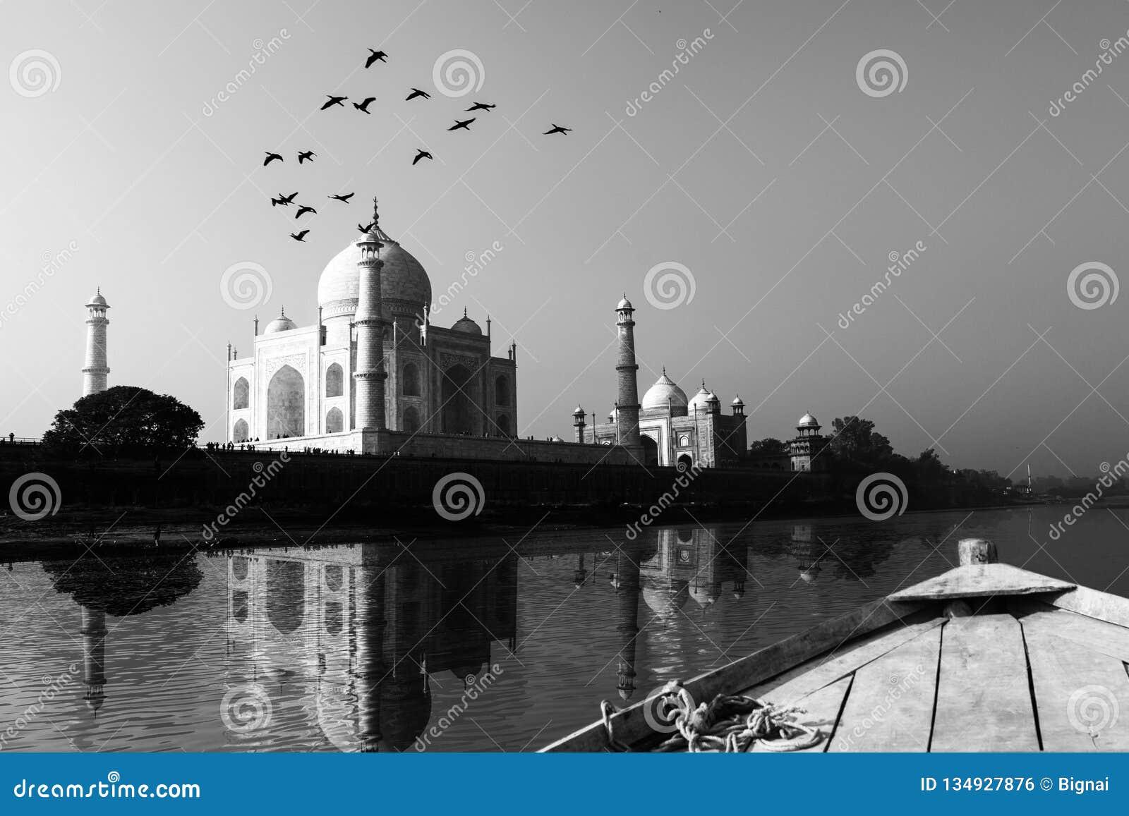 Taj Mahal in Yamuna-Riviermening wordt weerspiegeld van houten boot die in zwart-wit