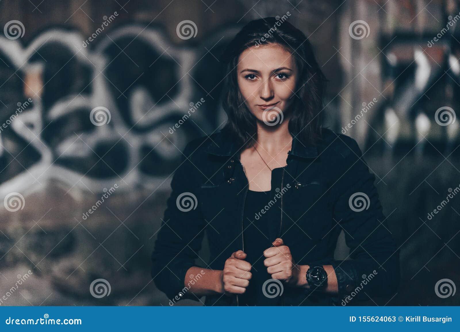 Tajemnicza piękna kobieta siedzi na starych kamieni krokach z w czarnym bodysuit i skórzana kurtka z henna tatuażem na ona nogi