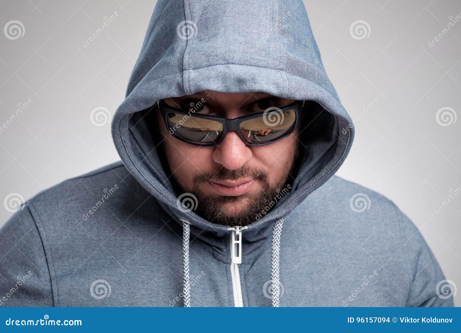 Tajemniczy brodaty mężczyzna w okularach przeciwsłonecznych chował pod kapiszonem