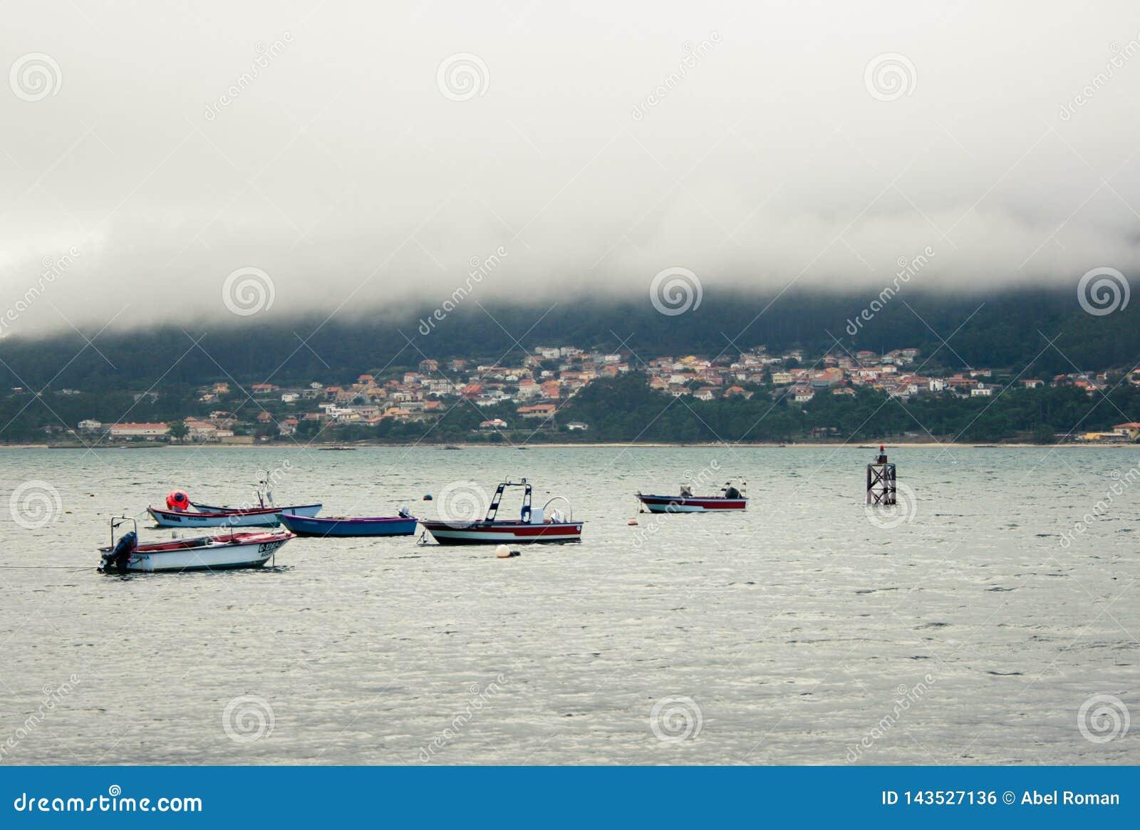 Tajemniczy morski miasteczko, łodzie i mgła,