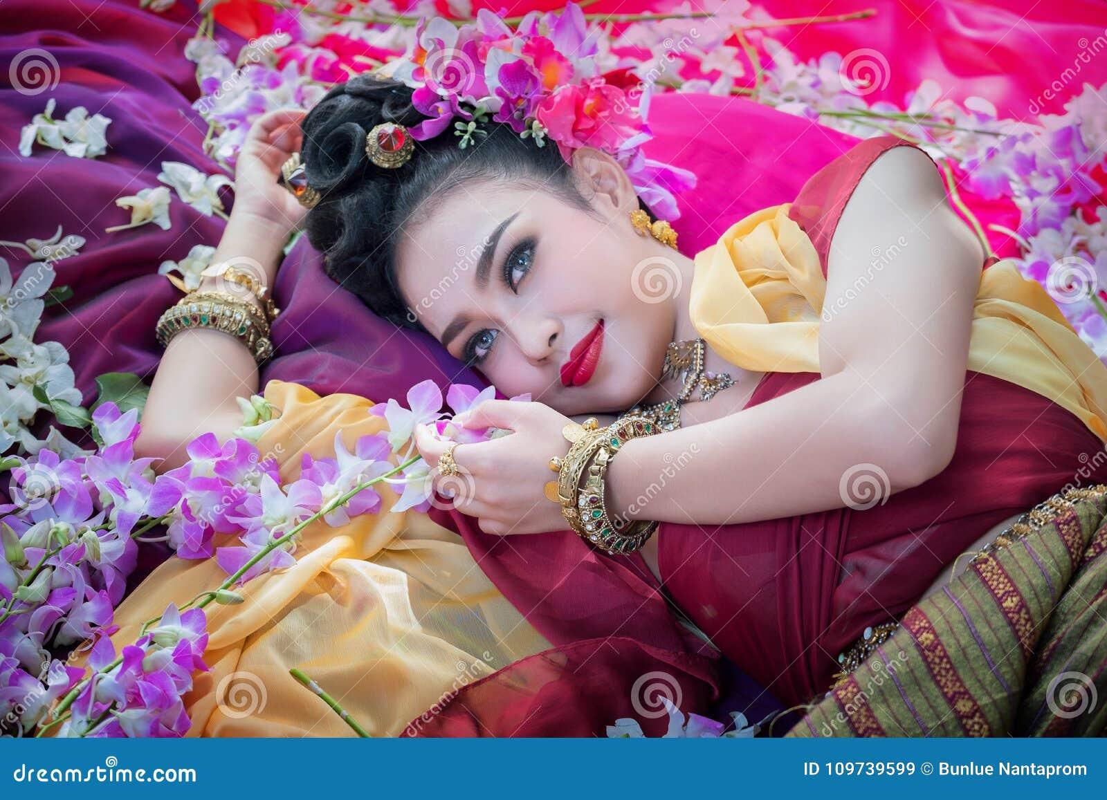 Tajlandzka kobieta jest ubranym trpical tajlandzką suknię z kwiatu tłem, po