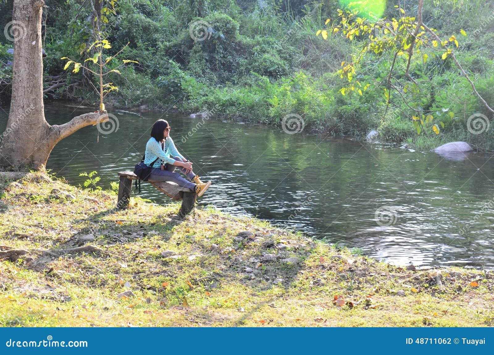 Tajlandzki kobieta portret siedzi na ławce przy lasem w Suan Phueng