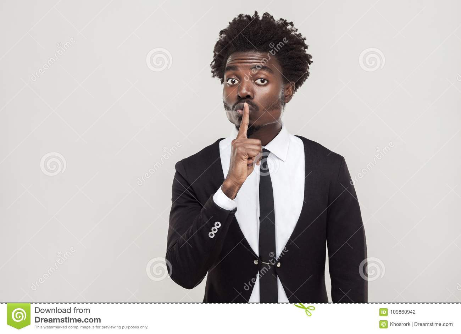Tajny lub spokojny pojęcie Afrykański biznesmen pokazuje znaka przy shh