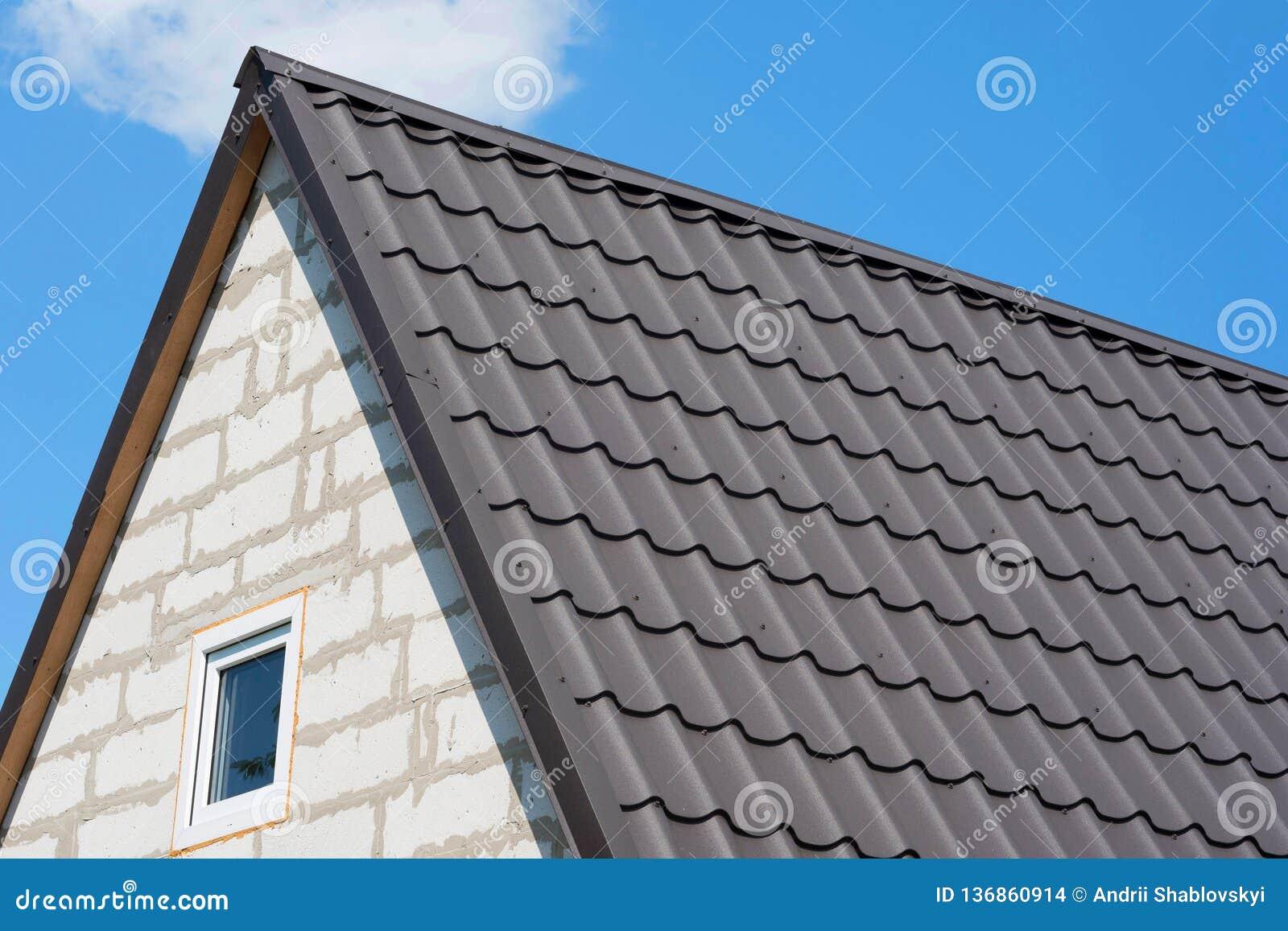 Tak av huset under bruna singlar Hörn av det oavslutade husslutet upp, mot bakgrunden av den blåa himlen