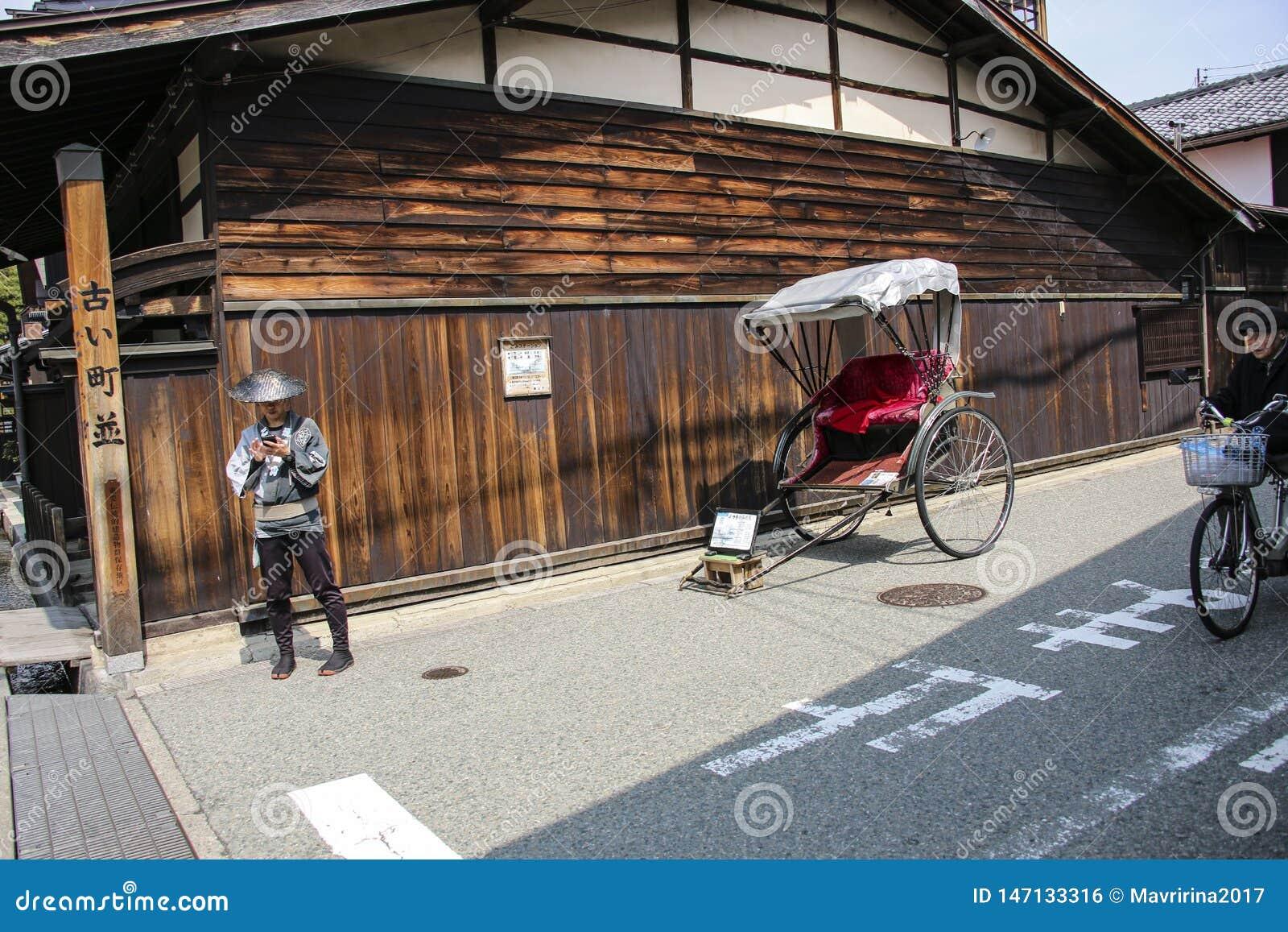 TAKAYAMA, JAPÓN - 27 DE MARZO DE 2019: Carro y carrito para los viajeros que caminan en las calles viejas Takayama, prefectura de