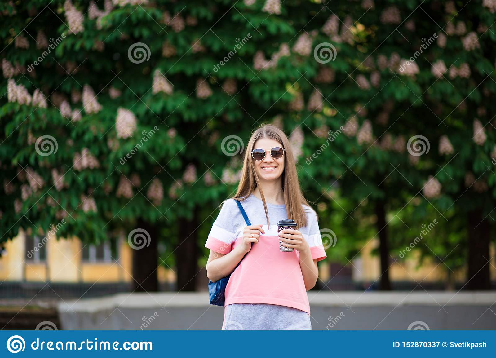 Take away coffee. Beautiful girl in sunglasses with backpack walk by summer street with coffee.