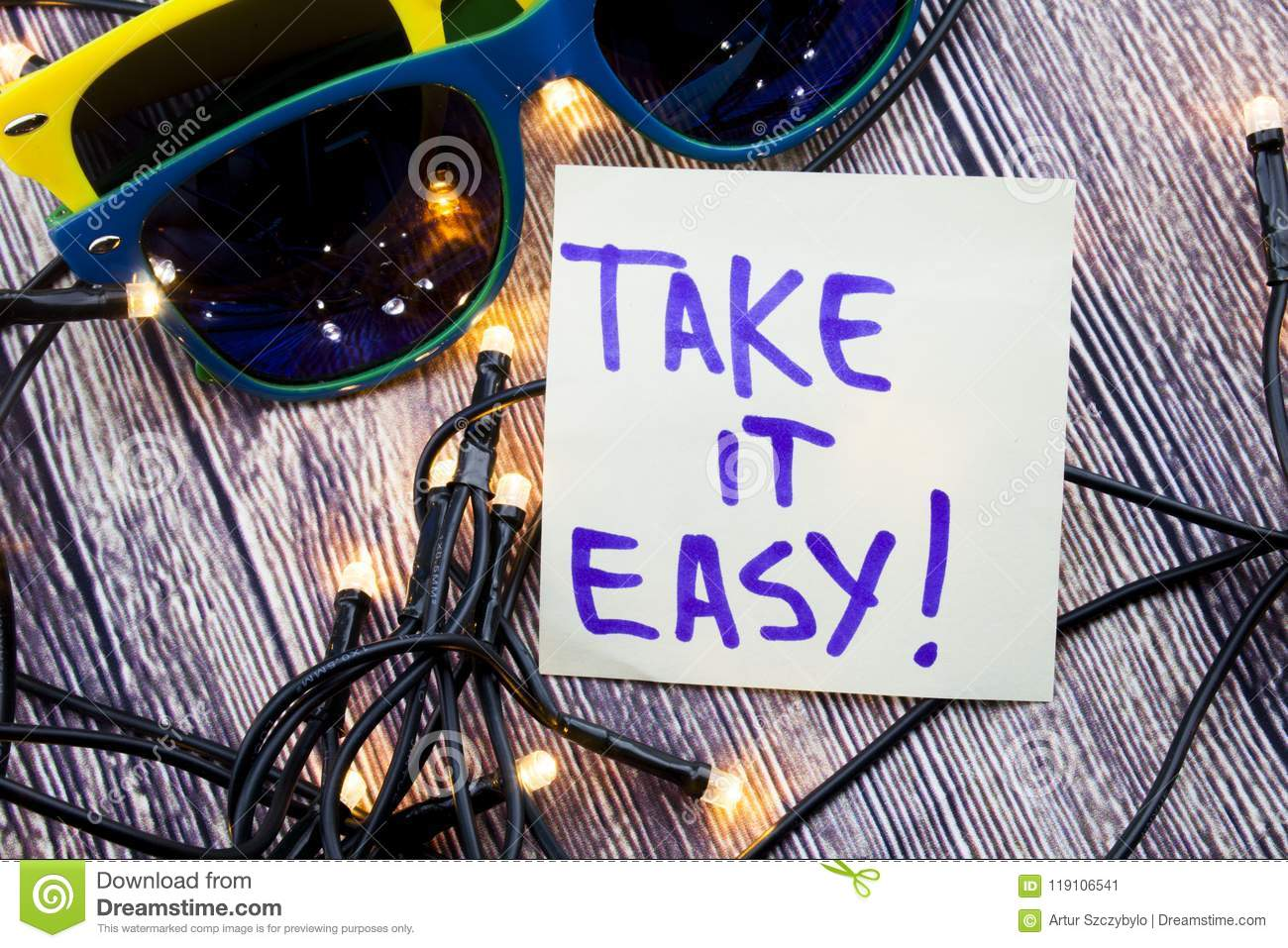 Take it easy A handwritten motivational quote. positive attitude words on the wooden background with two sunglasses of various col