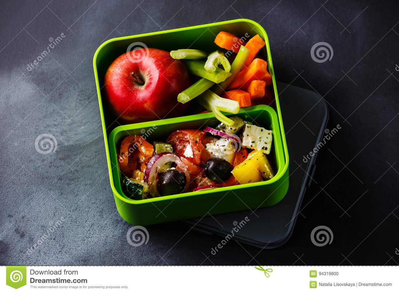 Take out food Greek salad and Apple fruit in Lunch box
