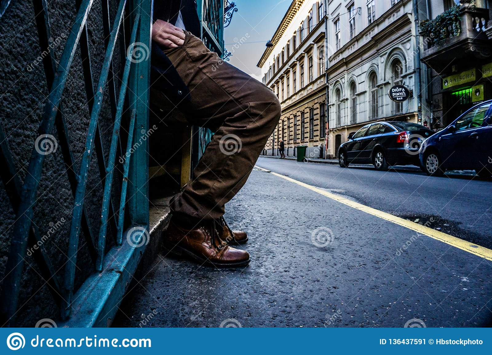 Legs and hand of a man reaching into his pocket on the streets of Budapest, Hungary with leading lines empasizing the act