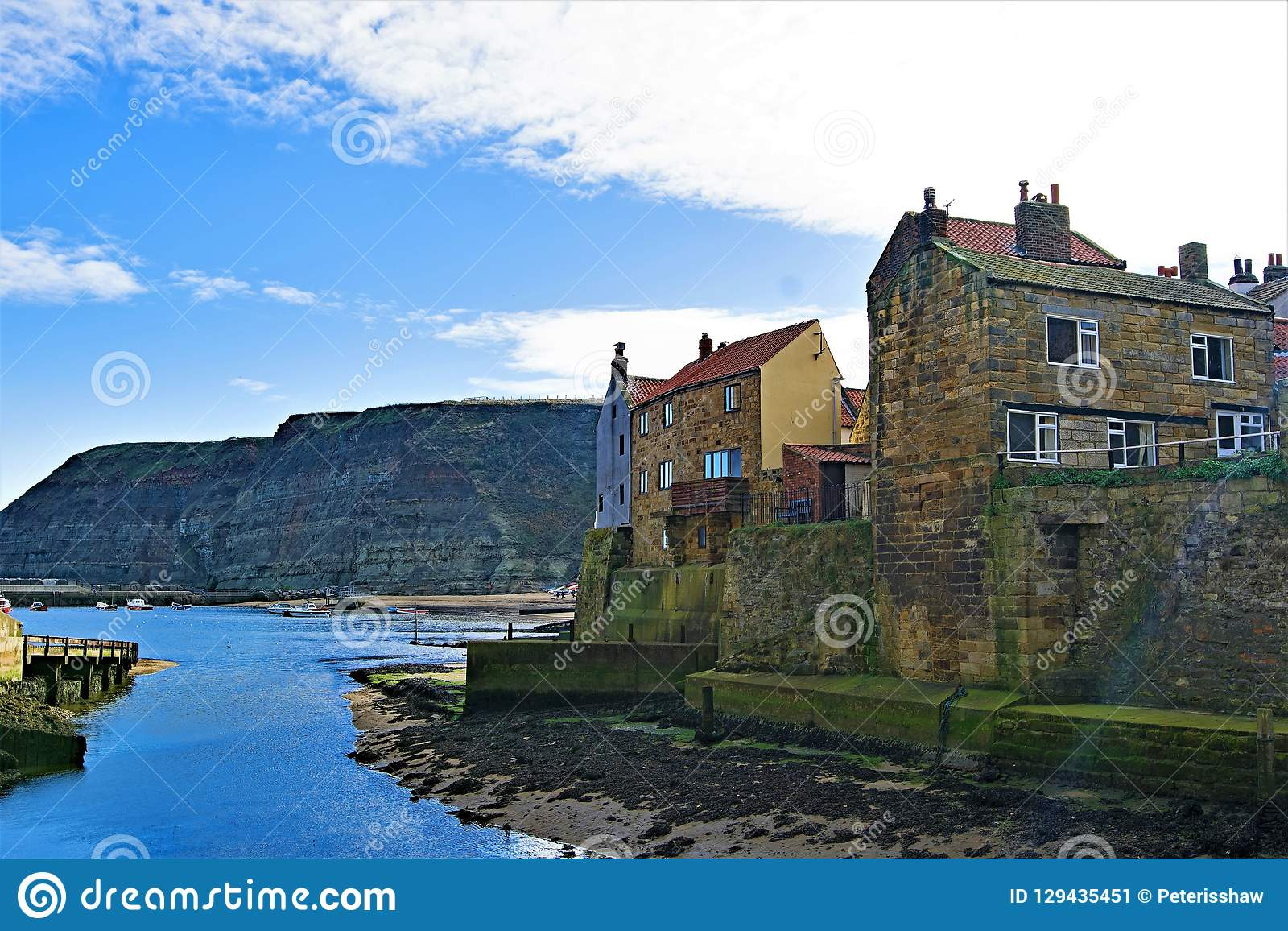 Inland view of Staithes harbour and Penny Nab, near Scarborough, in North Yorkshire.