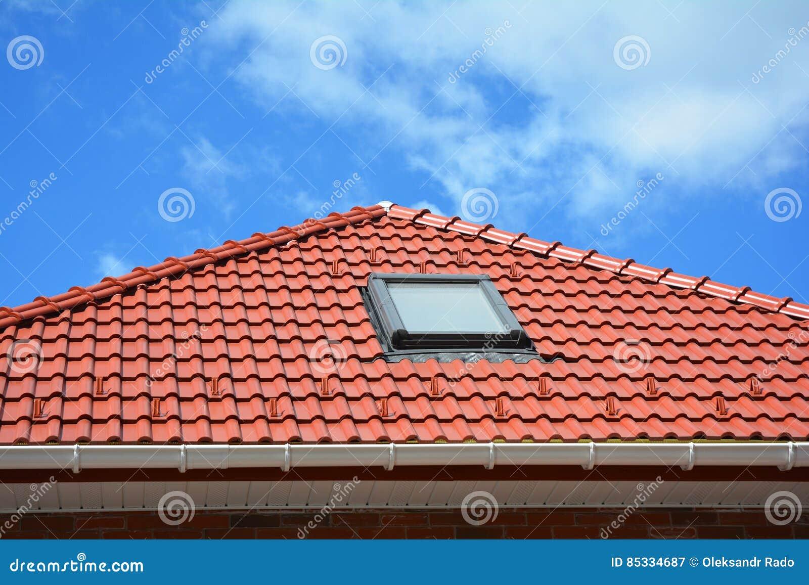 Takfönster på det röda hustaket för keramiska tegelplattor med stuprännan Takfönster, tak Windows och soltunneler Lofttakfönsterl