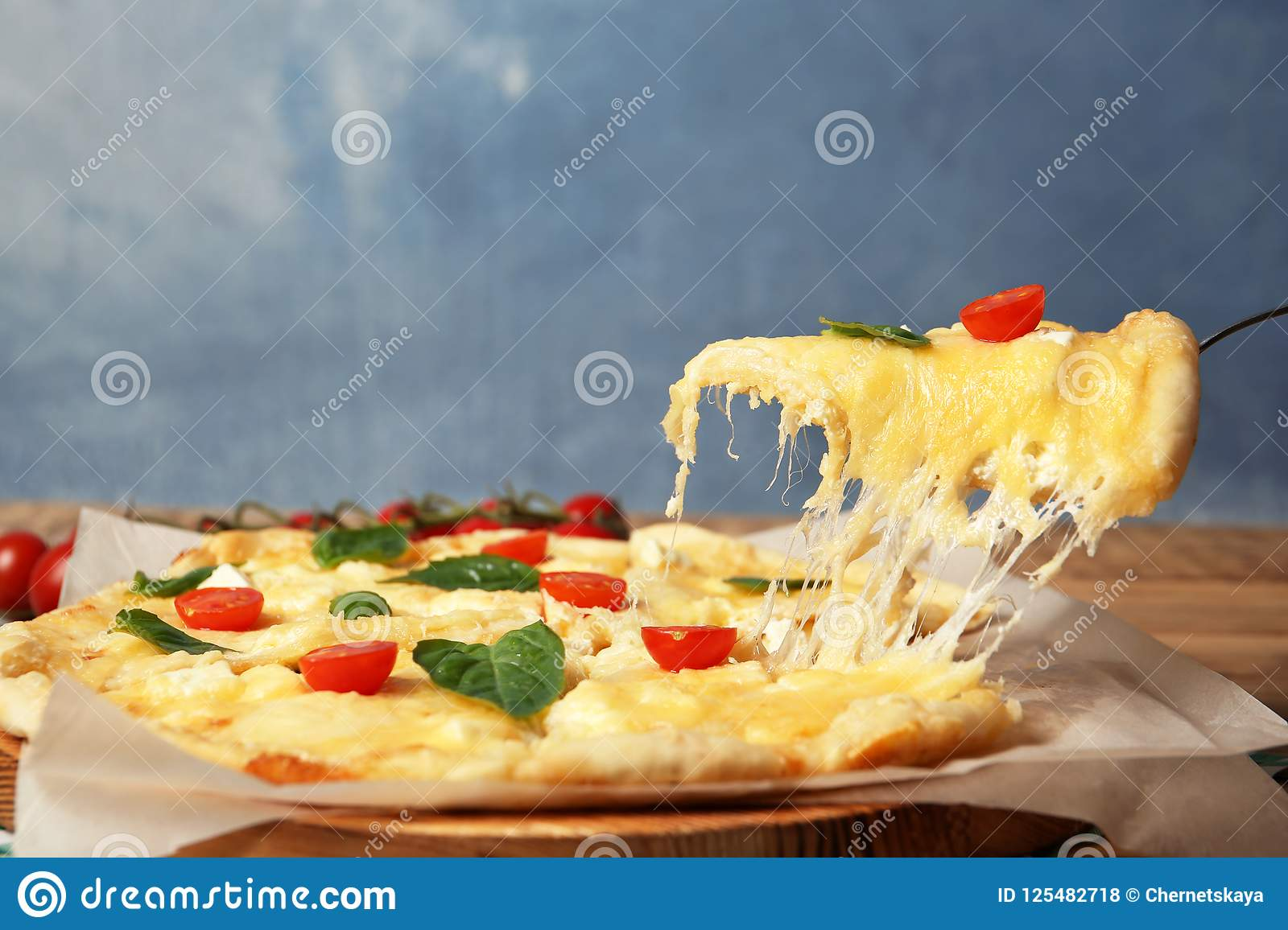 Taking tasty homemade pizza slice with melted cheese