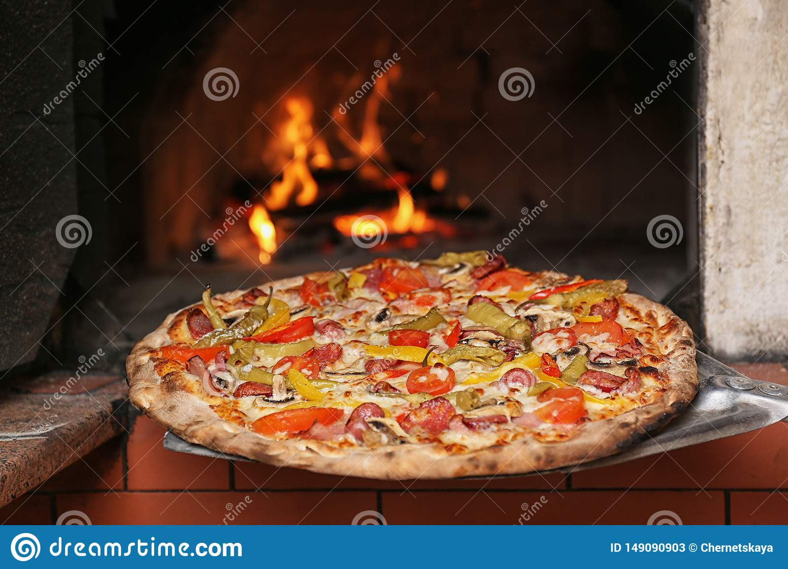Taking tasty pizza out of oven in restaurant