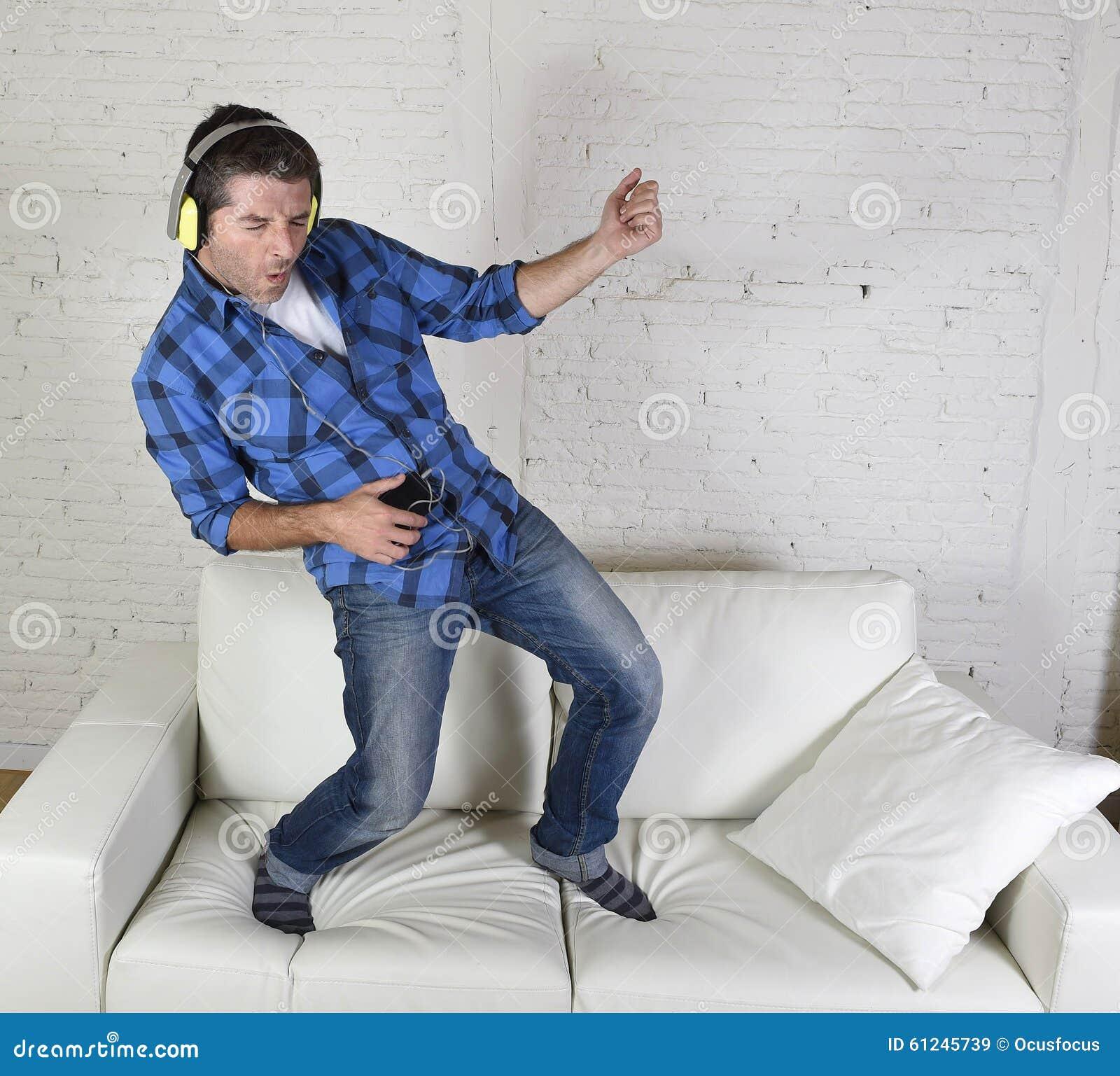 20-tal eller 30-talmannen hoppade på soffan som lyssnar till musik på mobiltelefonen med hörlurar som spelar Air Guitar