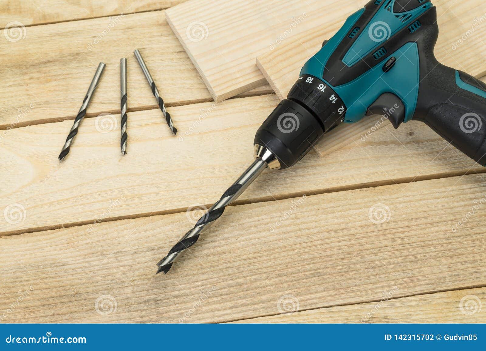 Taladro eléctrico en un fondo de madera Herramientas de la carpintería