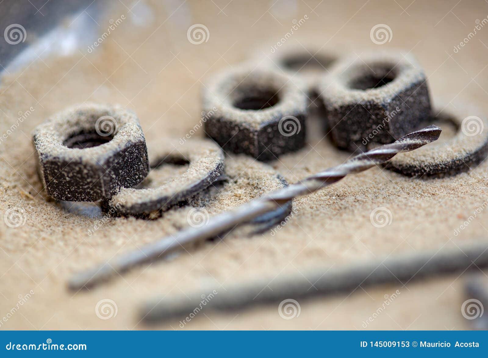 Taladro y algunas nueces y anillos de embalaje