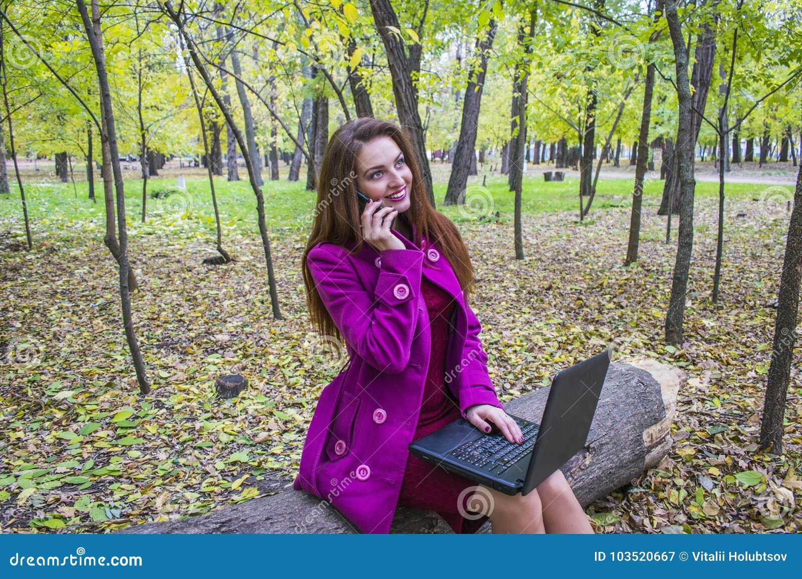 Talande kvinnabarn för telefon Närliggande är en bärbar dator