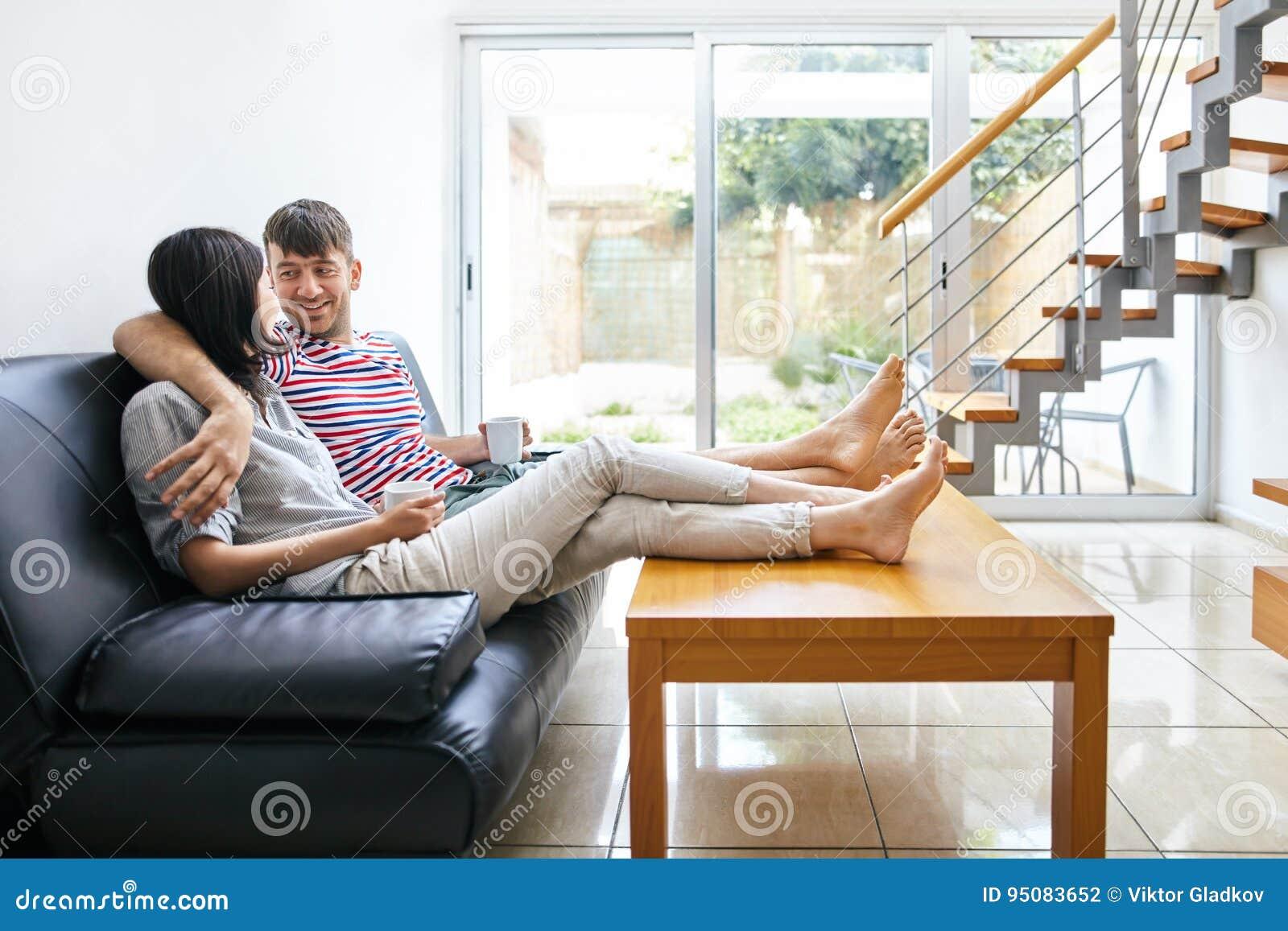 Talande sammanträde för lyckliga attraktiva par på soffan i modernt H