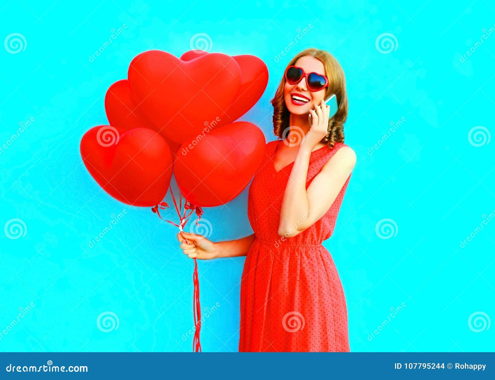 Talar den lyckliga skratta kvinnan för ståenden på telefonen med ballonger för en luft