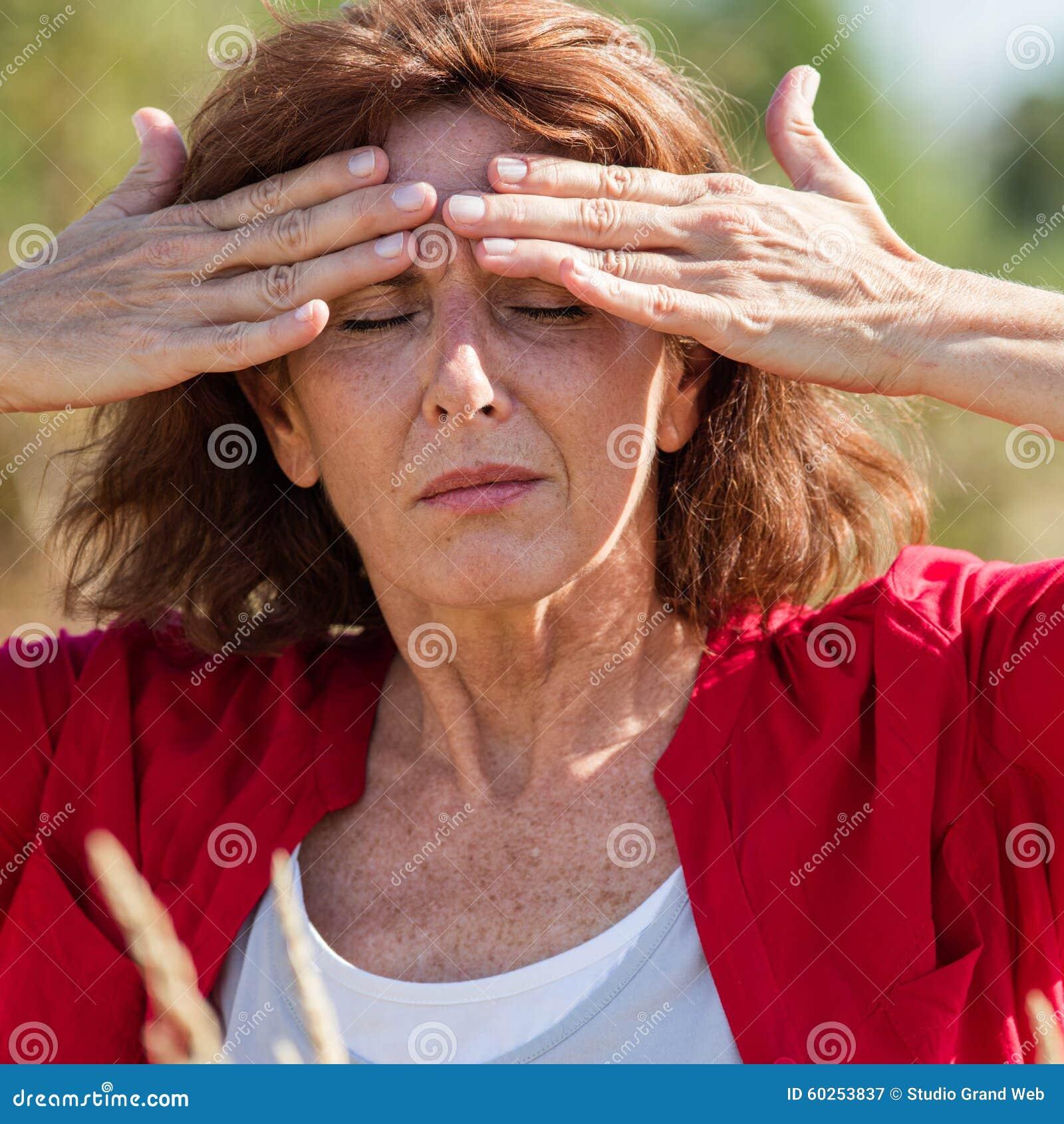 50-talbrunettkvinnan som masserar pannan för att lugna bihåla, smärtar utomhus