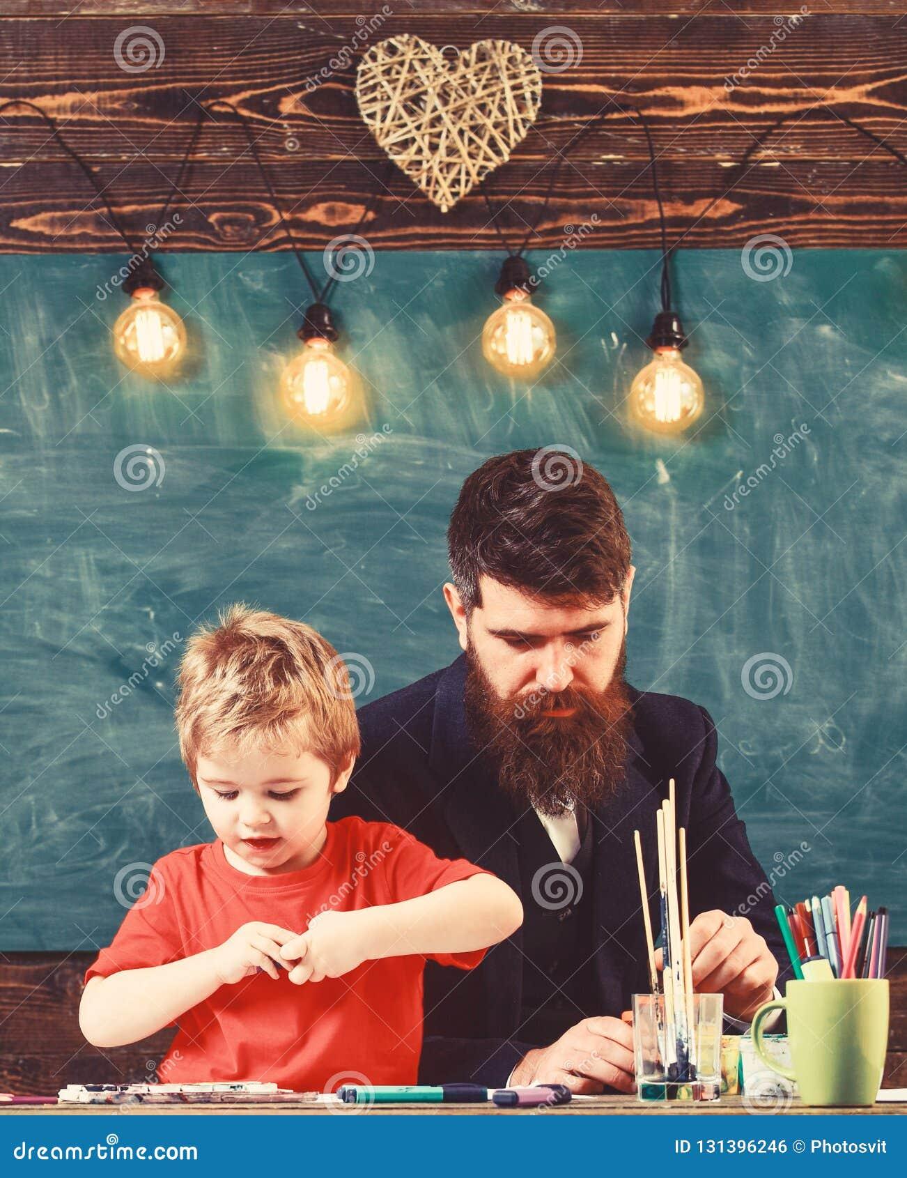 Talent en creativiteitconcept Kind en leraar die op bezige gezichten, het trekken schilderen Leraar met baard, vader en weinig
