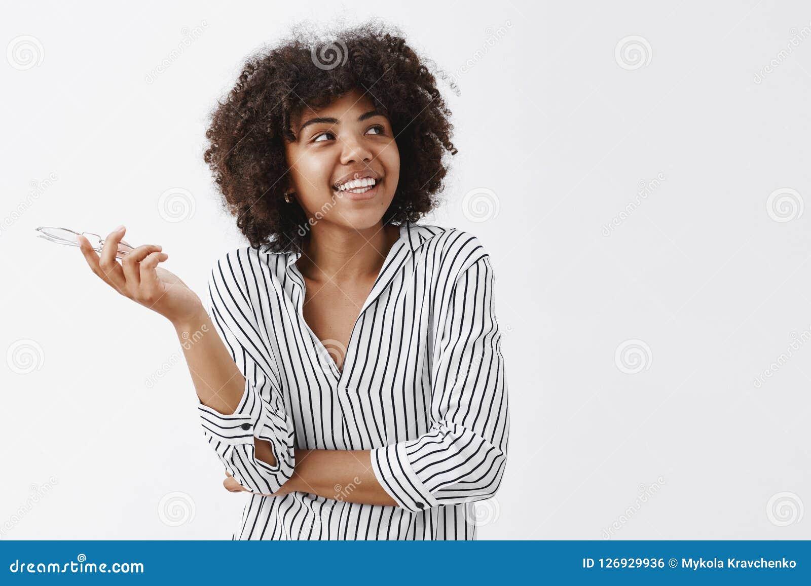 Talia strzelał szczęśliwy i beztroski nowożytny amerykanina afrykańskiego pochodzenia bizneswoman trzyma szkła wewnątrz w modnej