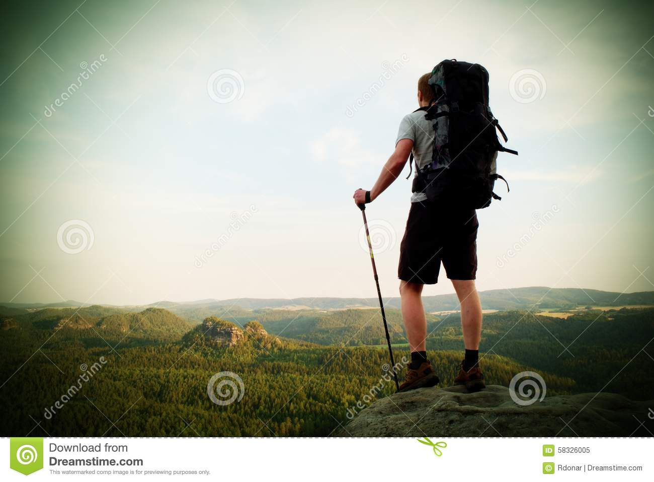 Tall backpacker with poles in hand. Sunny summer evenng in rocky mountains. Hiker with big backpack stand on rocky view point