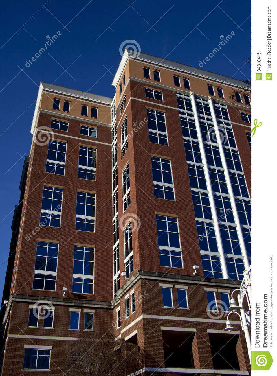 tall brick building with blue tinted windows coverd on two sides with crisp blue sky royalty. Black Bedroom Furniture Sets. Home Design Ideas