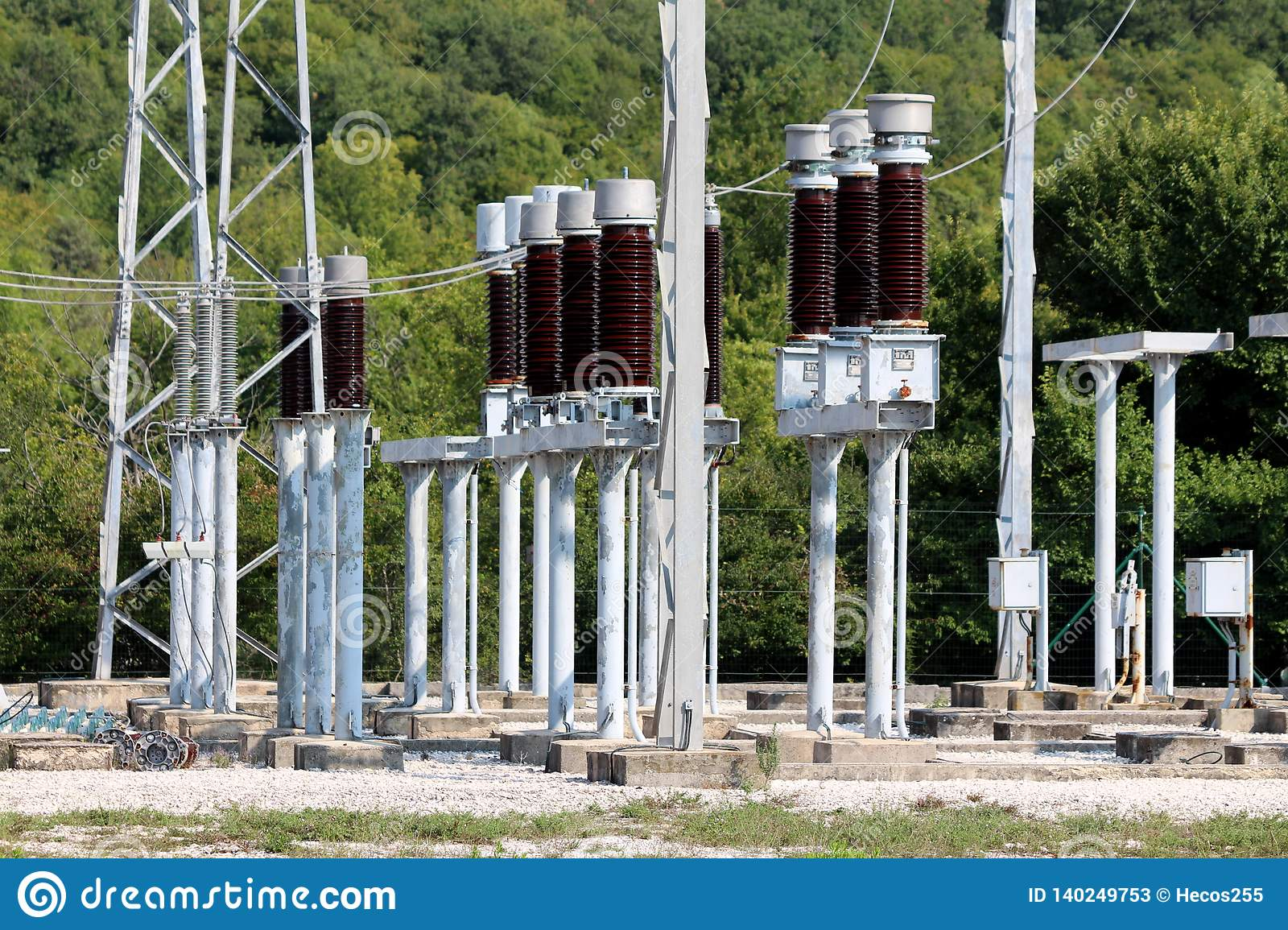 Tall dark brown ceramic insulators mounted on metal pipes and connected with electrical wires inside local power plant surrounded
