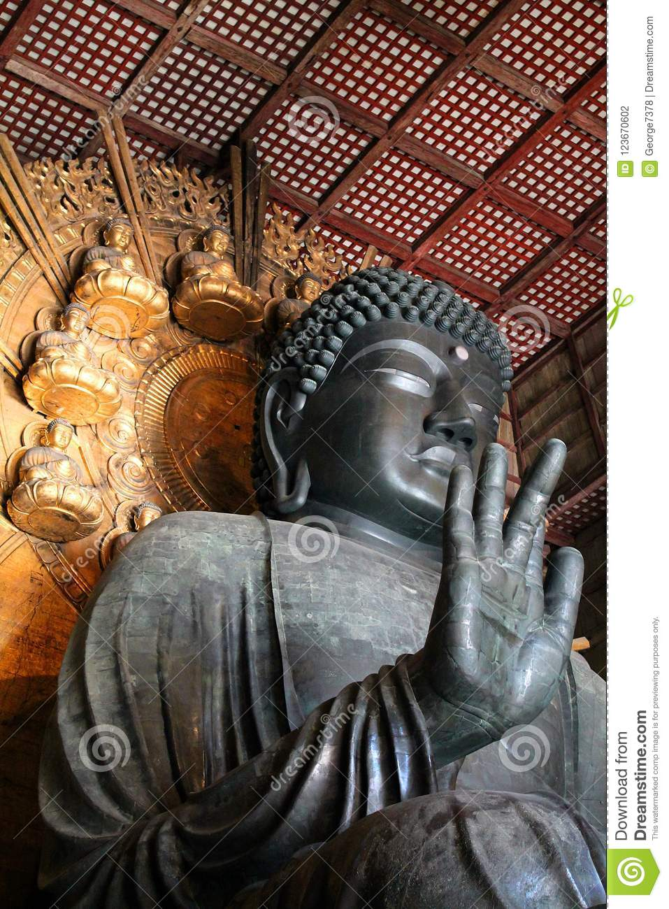 a6466f9c4d A tall metal Buddha figure sits with its right hand raised, palm pointing  forwards and middle finger slightly extended. The statue is inside the  wooden ...