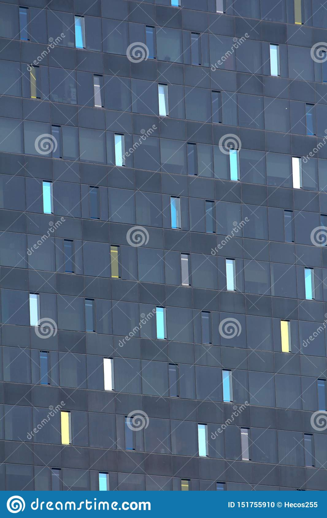 Tall narrow colorful windows on new dark modern office building texture background