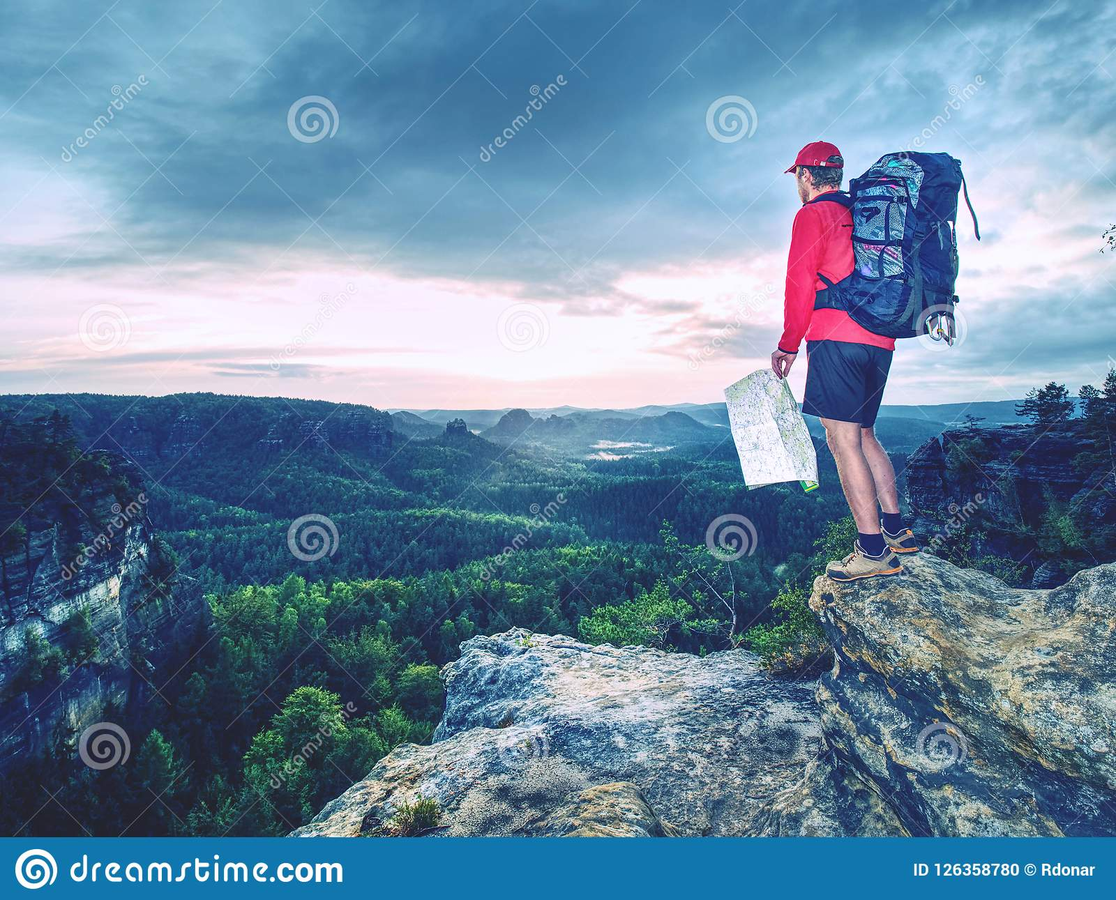 f57fedc10e1d Tall tourist with big backpack looking in paper map. Wild hilly nature  park. Hiker looking for new locations and landmarks to visit in map in his  hands