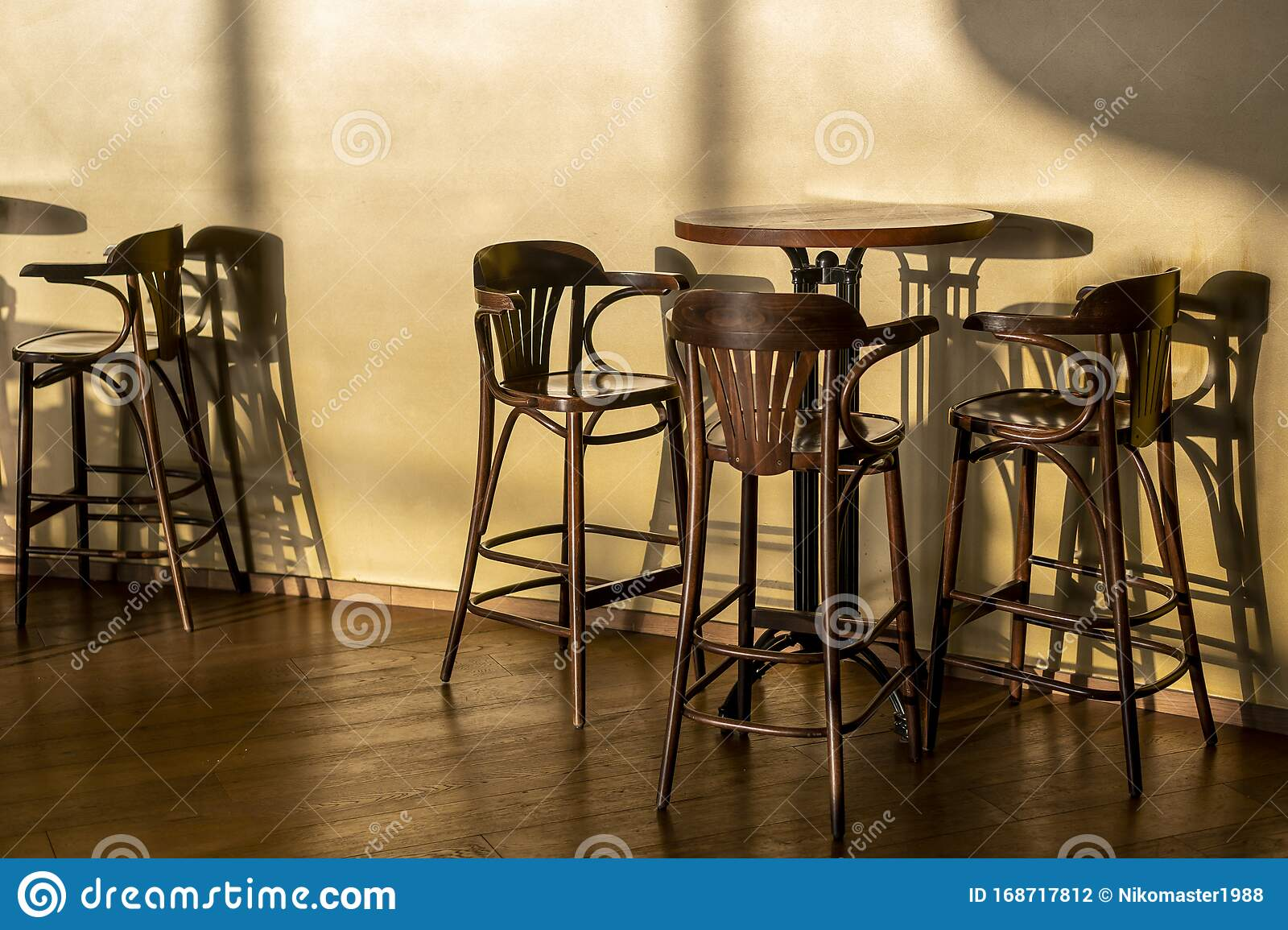 Picture of: Tall Vintage Wooden Table And Chairs Stand In A Cafe A Light Cool Shadow From Sunlight Reflects On The Wall And Floor A Clear Stock Photo Image Of Urban Vacation 168717812
