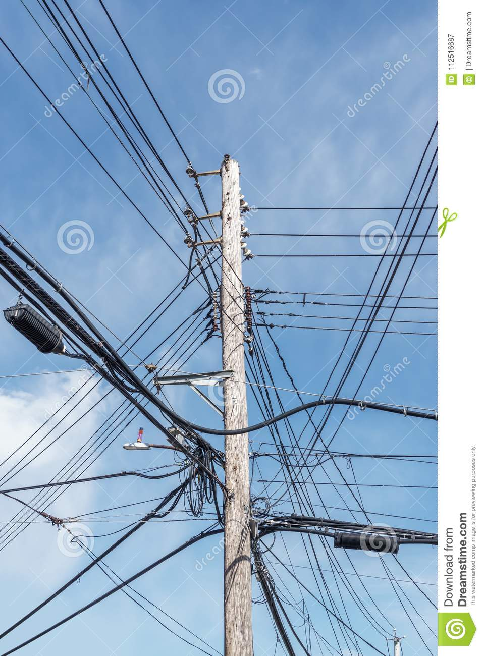 Tall Wooden Power Pole With Lots Of Overhead Wires, Coiled