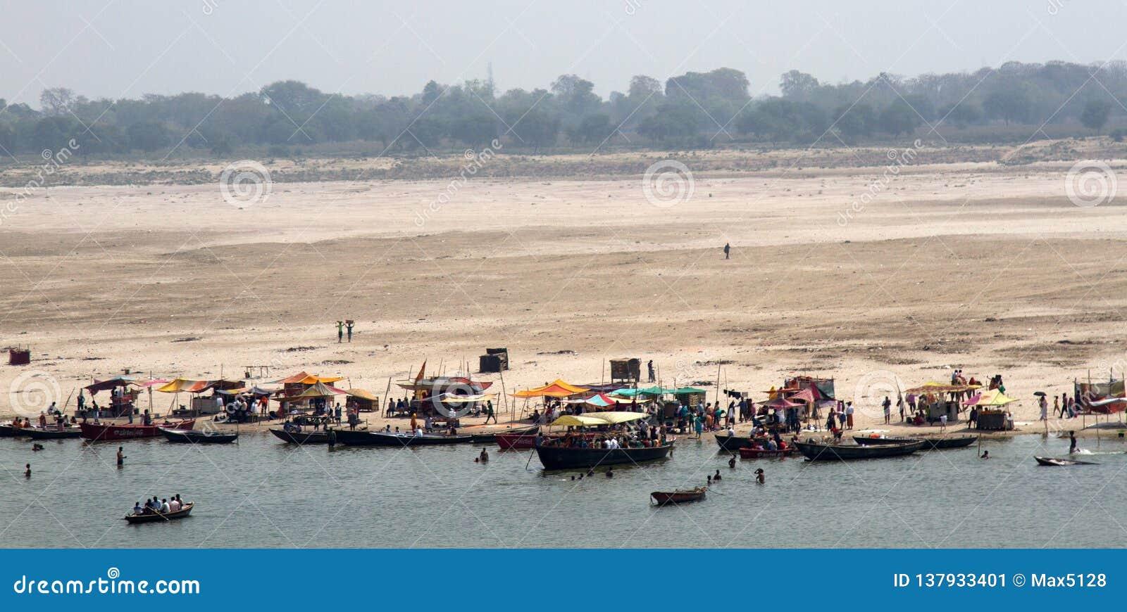 Talrikt vallfärdar för att utföra tvagning och att be i vatten av Ganges