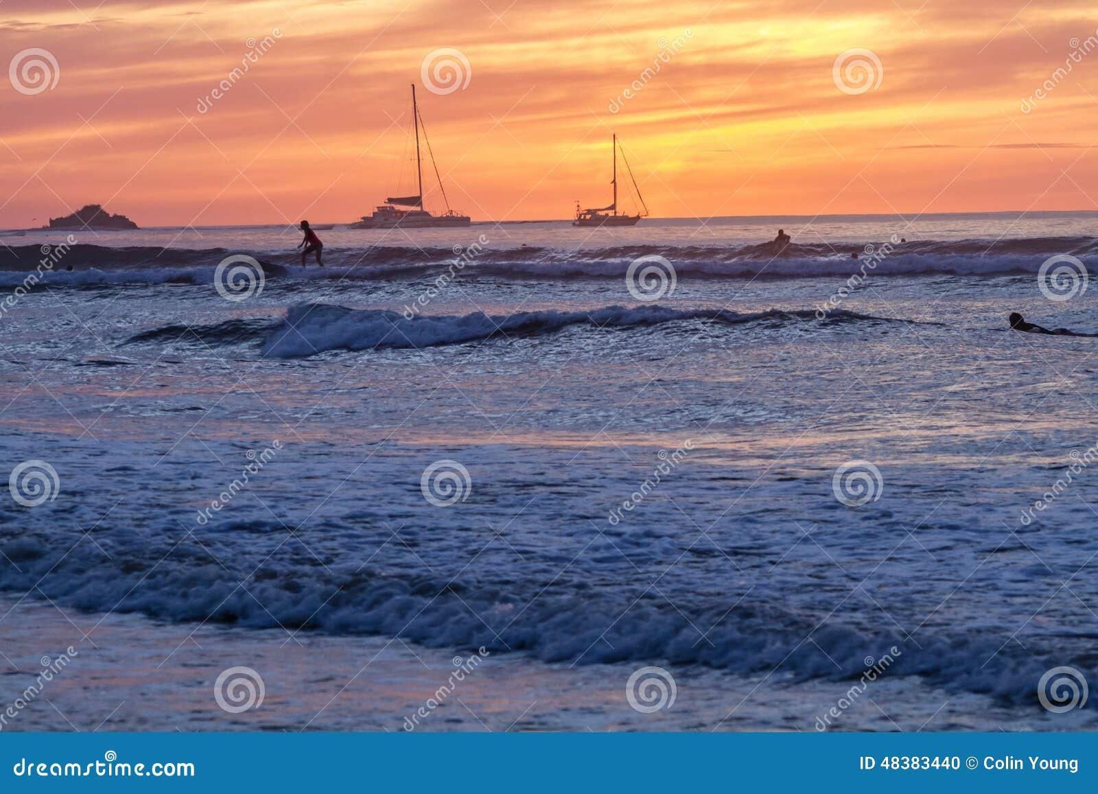 Tamarindo, der bei Sonnenuntergang surft