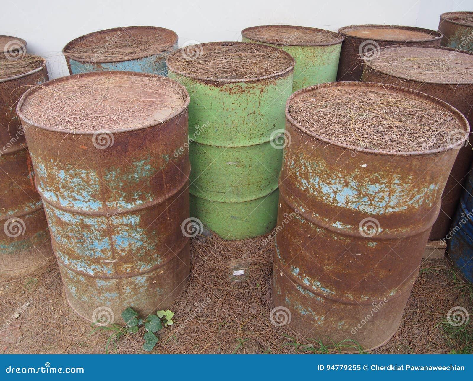 Tambores de óleo oxidados de corrosão abandonados na terra