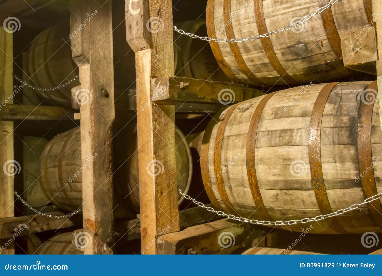 Tambores do bourbon do carvalho na cremalheira no armazém