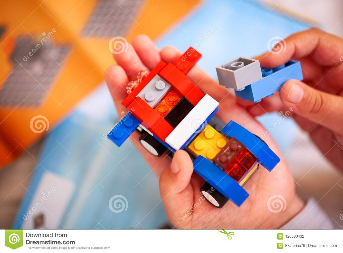 Child Building Lego Car There Are Some Lego Instructions On Ba