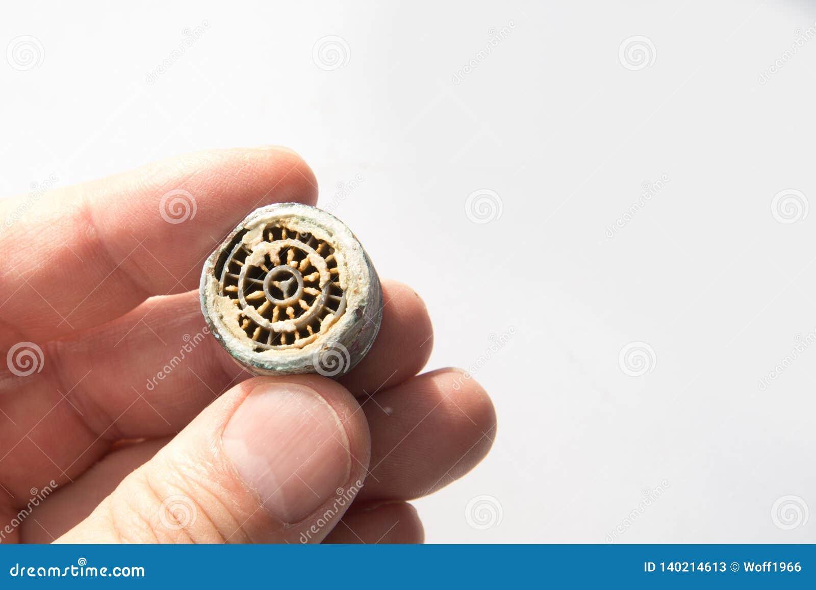 Tamis calcifié d un tamis faucetCalcined de la grue dans les mains sur un plan rapproché blanc de fond