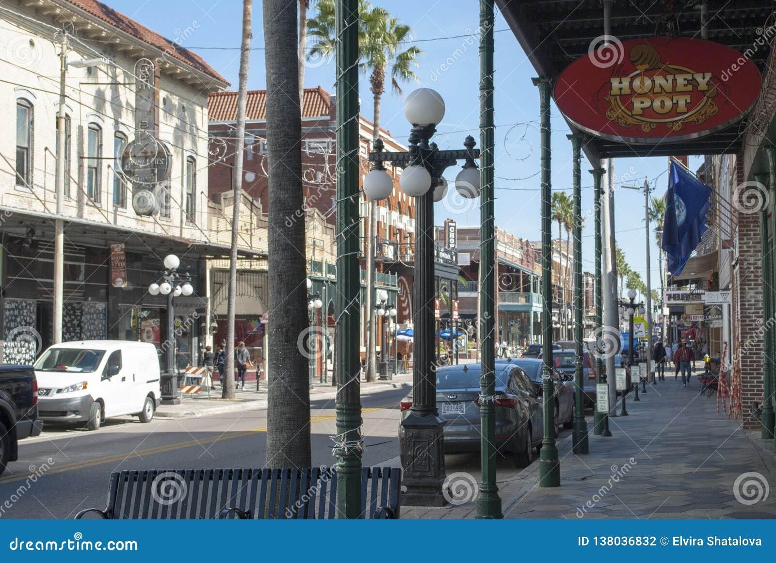 Tampa, calle famosa de la ciudad de Ybor 7ma con las tiendas, restaurantes, coches, el caminar de la gente