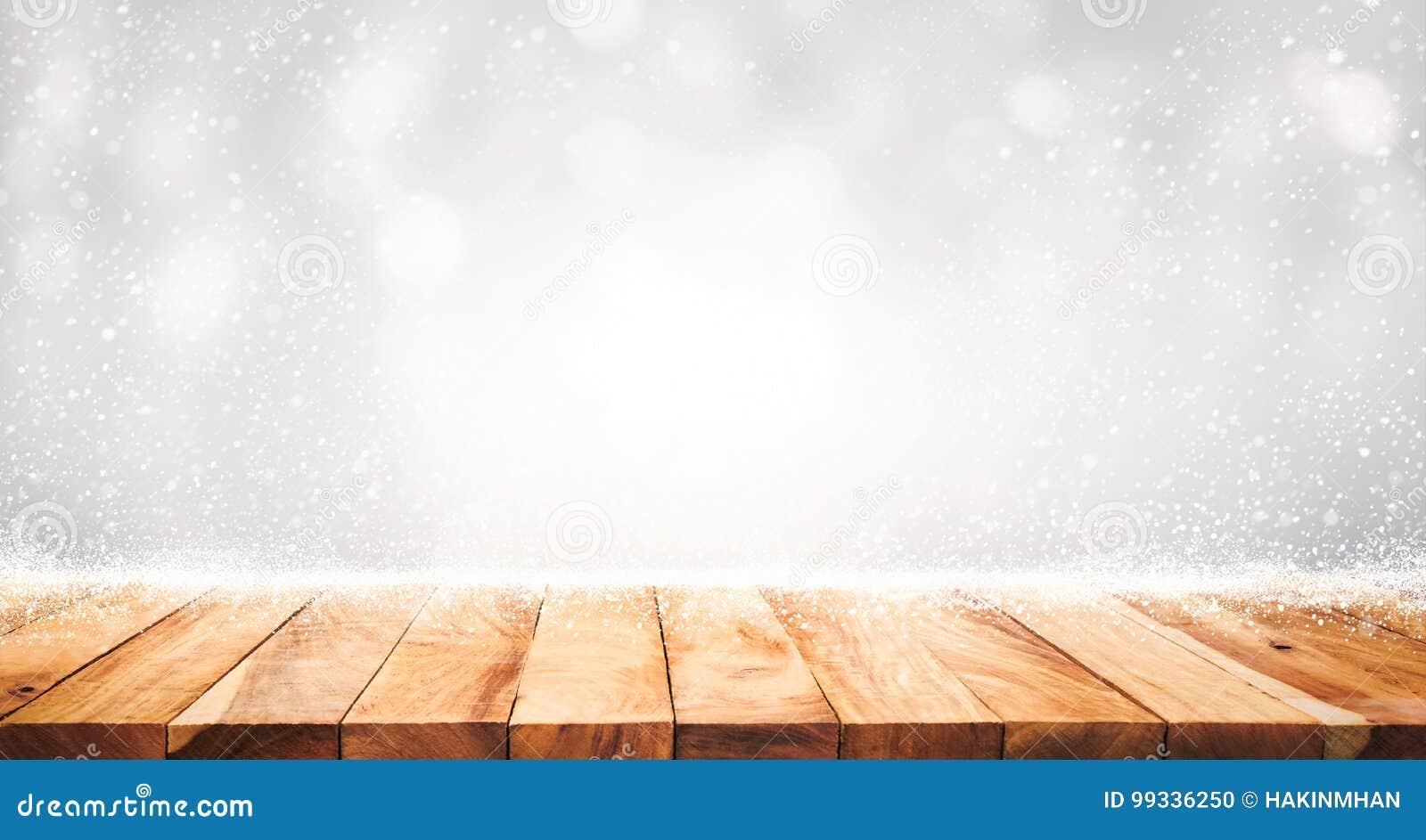 Tampo da mesa de madeira com queda de neve do fundo da estação do inverno Natal